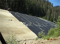 This photo shows installation of the geomembrane cover in progress at Tailing Pile 3.